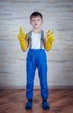 Χαριτωμένο αγόρι στα μεγάλου μεγέθους λαστιχένια γάντια Στοκ Εικόνες