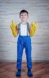 Χαριτωμένο αγόρι στα μεγάλου μεγέθους λαστιχένια γάντια Στοκ φωτογραφία με δικαίωμα ελεύθερης χρήσης