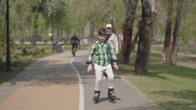 Χαριτωμένο αγόρι στα φωτεινά ενδύματα που στο πάρκο, ο παππούς του που περπατά πλησίον Ελεύθερος χρόνος υπαίθρια Το παιδί που έχε φιλμ μικρού μήκους