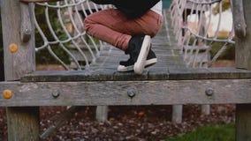 Χαριτωμένο αγόρι στη σειρά μαθημάτων σχοινιών πάρκων περιπέτειας Στοχαστικοί αρσενικοί περίπατοι παιδιών στη γέφυρα σχοινιών, εμπ απόθεμα βίντεο