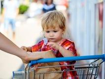 Χαριτωμένο αγόρι στο καροτσάκι αγορών Στοκ εικόνα με δικαίωμα ελεύθερης χρήσης
