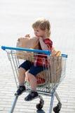 Χαριτωμένο αγόρι στο καροτσάκι αγορών Στοκ Φωτογραφία