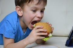 Χαριτωμένο αγόρι στο σπίτι στον καναπέ, που τρώει ένα χάμπουργκερ και που εξετάζει την ταμπλέτα, κινούμενα σχέδια προσοχής ή ομιλ Στοκ Εικόνες