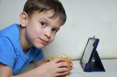 Χαριτωμένο αγόρι στο σπίτι στον καναπέ, που τρώει ένα χάμπουργκερ και που εξετάζει την ταμπλέτα, κινούμενα σχέδια προσοχής ή ομιλ Στοκ Εικόνα