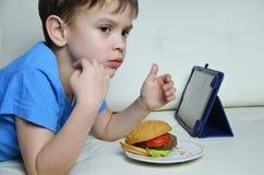 Χαριτωμένο αγόρι στο σπίτι στον καναπέ, που τρώει ένα χάμπουργκερ και που εξετάζει την ταμπλέτα, κινούμενα σχέδια προσοχής ή ομιλ Στοκ Φωτογραφία