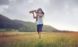 Χαριτωμένο αεροπλάνο παιχνιδιών μικρών παιδιών παίζοντας στοκ εικόνες
