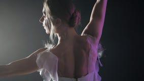 Χαριτωμένο αισθησιακό ballerina στα άσπρα χορεύοντας στοιχεία φορεμάτων tutu του κλασσικού ή σύγχρονου μπαλέτου στο σκοτάδι με τη απόθεμα βίντεο