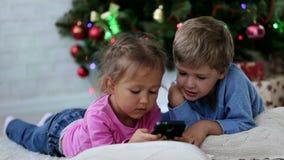 Χαριτωμένο αμφιθαλών somethng αστείο στο κινητό τηλέφωνο κοντά στο χριστουγεννιάτικο δέντρο απόθεμα βίντεο