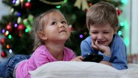 Χαριτωμένο αμφιθαλών somethng αστείο στο κινητό τηλέφωνο κοντά στο χριστουγεννιάτικο δέντρο φιλμ μικρού μήκους