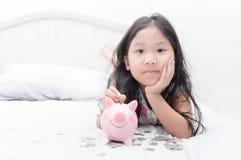 Χαριτωμένο ασιατικό κορίτσι που βάζει το νόμισμα στη piggy τράπεζα στο κρεβάτι Στοκ Φωτογραφία