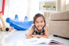 Χαριτωμένο ασιατικό κορίτσι που διαβάζει ένα βιβλίο και που χαμογελά το λευκό δοντιών ενώ στο ζωντανό δωμάτιο Στοκ Εικόνα