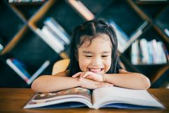 Χαριτωμένο ασιατικό κορίτσι που διαβάζει ένα βιβλίο και που χαμογελά το λευκό δοντιών ενώ στο ζωντανό δωμάτιο Στοκ Εικόνες