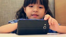 Χαριτωμένο ασιατικό κορίτσι που παίζει το έξυπνο τηλέφωνο απόθεμα βίντεο