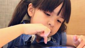 Χαριτωμένο ασιατικό κορίτσι που παίζει το έξυπνο τηλέφωνο φιλμ μικρού μήκους