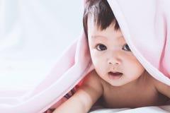 Χαριτωμένο ασιατικό κοριτσάκι που χαμογελά κάτω από το ρόδινο κάλυμμα Στοκ φωτογραφία με δικαίωμα ελεύθερης χρήσης