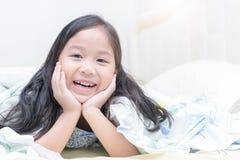 Χαριτωμένο ασιατικό χαμόγελο κοριτσιών και να βρεθεί στο κρεβάτι Στοκ εικόνες με δικαίωμα ελεύθερης χρήσης