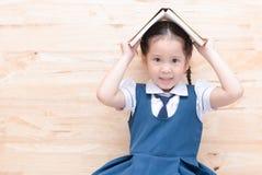 Χαριτωμένο ασιατικό χαμόγελο κοριτσιών με το βιβλίο στο κεφάλι στο ξύλινο υπόβαθρο Στοκ Εικόνες