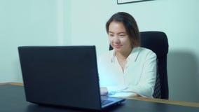 Χαριτωμένο ασιατικό lap-top χρήσης κοριτσιών στον πίνακα στην αρχή απόθεμα βίντεο