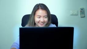 Χαριτωμένο ασιατικό lap-top χρήσης κοριτσιών στον πίνακα στην αρχή στοκ εικόνα με δικαίωμα ελεύθερης χρήσης