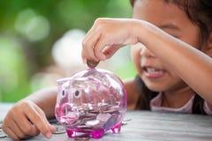 Χαριτωμένο ασιατικό lgirl που βάζει τα χρήματα στη piggy τράπεζα στοκ φωτογραφίες