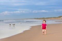 Χαριτωμένο αστείο κοριτσάκι που τρέχει στην όμορφη παραλία στοκ φωτογραφία