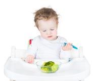 Χαριτωμένο αστείο μικρό παιδί σε μια άσπρη υψηλή καρέκλα που τρώει τα λαχανικά της φ στοκ φωτογραφία με δικαίωμα ελεύθερης χρήσης