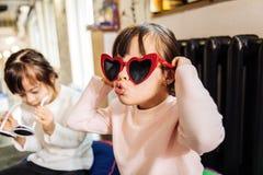 Χαριτωμένο αστείο σκοτεινός-μαλλιαρό κορίτσι που φορά τα φωτεινά κόκκινα γυαλιά ηλίου στοκ φωτογραφίες