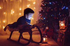 Χαριτωμένο λατρευτό αγόρι που διαβάζει ένα βιβλίο μπροστά από το χριστουγεννιάτικο δέντρο, Στοκ φωτογραφίες με δικαίωμα ελεύθερης χρήσης