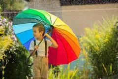Χαριτωμένο λατρευτό παιδί, αγόρι, που παίζει με τη ζωηρόχρωμη ομπρέλα κάτω από το s Στοκ εικόνα με δικαίωμα ελεύθερης χρήσης