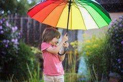 Χαριτωμένο λατρευτό παιδί, αγόρι, που παίζει με τη ζωηρόχρωμη ομπρέλα κάτω από το s Στοκ Εικόνες