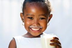 Χαριτωμένο αφρικανικό κορίτσι που παρουσιάζει άσπρο γάλα mustache στοκ εικόνες