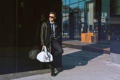 Χαριτωμένο ενήλικο άτομο που στέκεται κοντά στο μαύρο τοίχο και που κοιτάζει κατά μέρος Στοκ εικόνες με δικαίωμα ελεύθερης χρήσης
