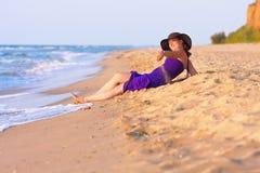 Χαριτωμένο λευκό κορίτσι που βάζει στην άμμο στην παραλία Στοκ Εικόνες