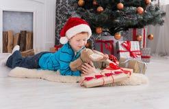 Χαριτωμένο ευτυχές αγόρι στο καπέλο santa με τα χριστουγεννιάτικα δώρα παιχνιδιών Στοκ Φωτογραφία