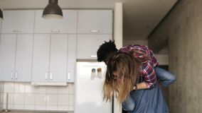 Χαριτωμένο ευτυχές ζεύγος Ο όμορφος τύπος mullato ανυψώνει επάνω και φέρνει τη γελώντας φίλη του γύρω από το διαμέρισμα απόθεμα βίντεο