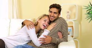 Χαριτωμένο ευτυχές ζεύγος που στηρίζεται μαζί στον καναπέ φιλμ μικρού μήκους