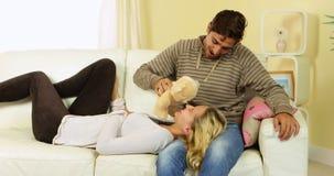 Χαριτωμένο ευτυχές ζεύγος που χαλαρώνει και που κουβεντιάζει μαζί στον καναπέ απόθεμα βίντεο