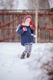 Χαριτωμένο ευτυχές κορίτσι παιδιών με την καραμέλα Χριστουγέννων στο χειμερινό χιονώδη κήπο Στοκ φωτογραφία με δικαίωμα ελεύθερης χρήσης