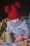 Χαριτωμένο ευτυχές κορίτσι παιδιών στη συνεδρίαση καπέλων και πουλόβερ Χριστουγέννων υπαίθρια Στοκ Φωτογραφίες