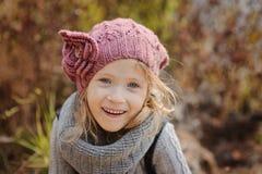Χαριτωμένο ευτυχές κορίτσι παιδιών στο πλεκτό πορτρέτο καπέλων και φιλέδων το φθινόπωρο Στοκ εικόνα με δικαίωμα ελεύθερης χρήσης