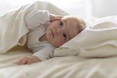 Χαριτωμένο ευτυχές κοριτσάκι 7 μηνών στην πάνα που βρίσκεται και που παίζει Στοκ Εικόνα