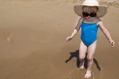 Χαριτωμένο ευτυχές κοριτσάκι που φορά το κολυμπώντας κοστούμι, γυαλιά ήλιων, καπέλο Στοκ φωτογραφία με δικαίωμα ελεύθερης χρήσης