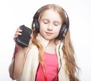 Χαριτωμένο ευτυχές μικρό κορίτσι με τα ακουστικά στοκ φωτογραφία με δικαίωμα ελεύθερης χρήσης