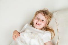 Χαριτωμένο ευτυχές μικρό κορίτσι που βάζει στο πάτωμα πέρα από το λευκό Στοκ Εικόνα