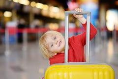 Χαριτωμένο ευτυχές μικρό παιδί με τη μεγάλη κίτρινη βαλίτσα στο διεθνή αερολιμένα πριν από την πτήση Στοκ Εικόνες
