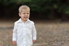 Χαριτωμένο ευτυχές μικρό παιδί στο άσπρο πουκάμισο Στοκ Φωτογραφία