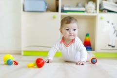 Χαριτωμένο ευτυχές παιχνίδι μωρών χαμόγελου με τα ζωηρόχρωμα παιχνίδια κουδουνισμάτων Νέος - γεννημένο παιδί, σύρσιμο εκμάθησης μ στοκ εικόνα