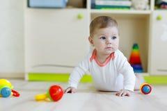 Χαριτωμένο ευτυχές παιχνίδι μωρών χαμόγελου με τα ζωηρόχρωμα παιχνίδια κουδουνισμάτων Νέος - γεννημένο παιδί, σύρσιμο εκμάθησης μ στοκ φωτογραφία με δικαίωμα ελεύθερης χρήσης