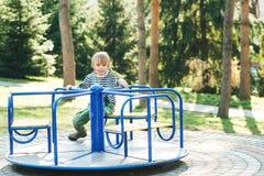 Χαριτωμένο ευτυχές παιδί Παιχνίδι αγοριών στην παιδική χαρά σε ένα πάρκο Στοκ Εικόνα