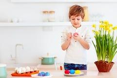 Χαριτωμένο ευτυχές παιδί που χρωματίζει τα αυγά Πάσχας στο γραφείο κουζινών Στοκ Εικόνες
